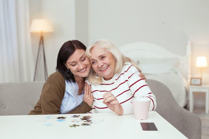 快乐会集难题的老妇人和照料者 免版税库存照片