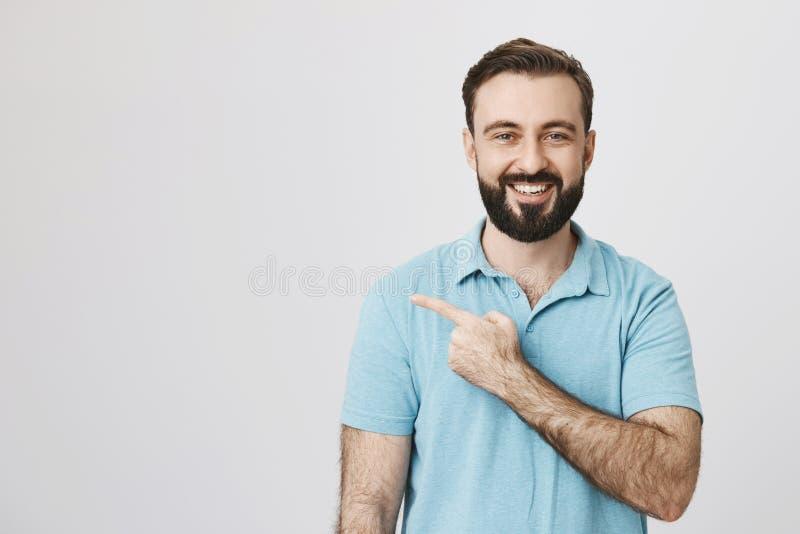 快乐地微笑愉快的成人欧洲的人,当指向左与食指,在灰色背景时 题材的人 库存图片