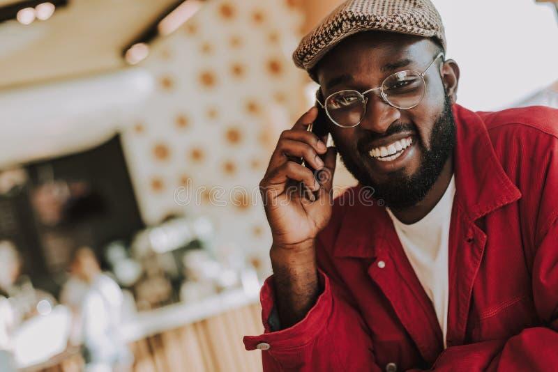 快乐地微笑有胡子的年轻人谈话在电话和 免版税图库摄影