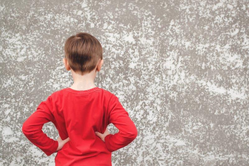 快乐孩子看灰色墙的后视 灰色混凝土墙背景 莫库普 免版税库存图片