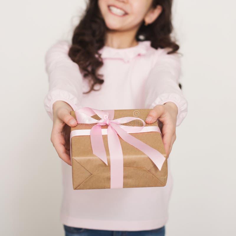 快乐小女孩给在白色背景 免版税库存照片