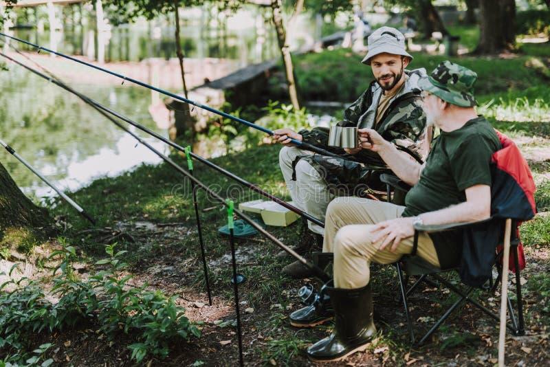 快乐的一起钓鱼在河岸的父亲和儿子 免版税库存照片