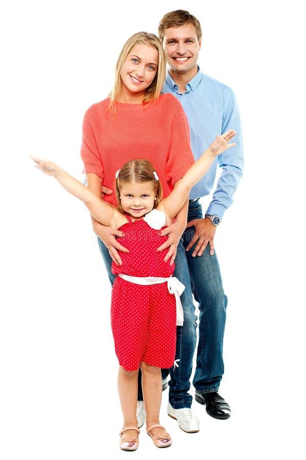 快乐的三口之家摆在户内 免版税库存图片