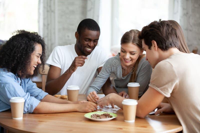快乐的不同的坐在桌上的人民聚集的难题 免版税图库摄影