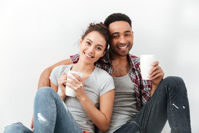 快乐的不同种族的年轻夫妇饮用的咖啡和拥抱 库存图片