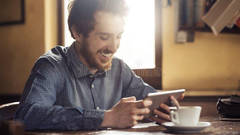 快乐的与他的片剂的行家社会网络 免版税库存照片