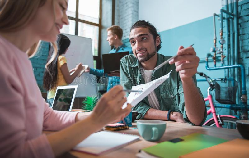 快乐的专业工作者在办公室谈论项目 免版税库存照片