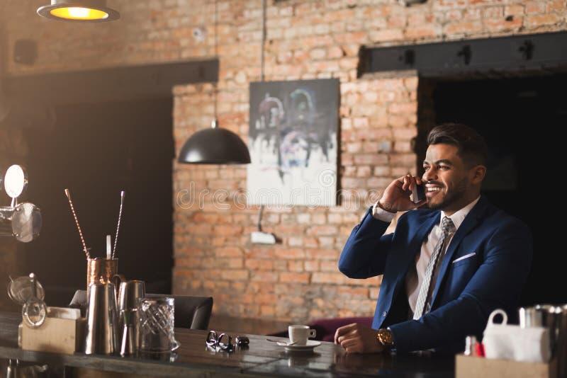 快乐的事务谈话在酒吧的电话 免版税库存照片