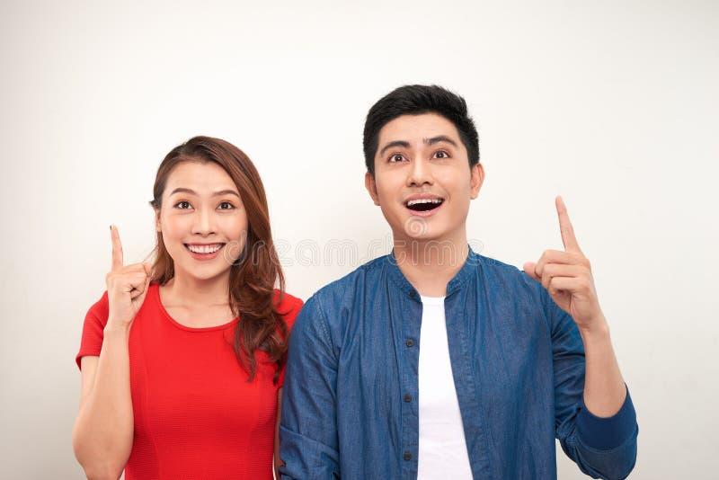 快乐的亚洲夫妇身分被隔绝在白色背景,指向手指 免版税库存图片