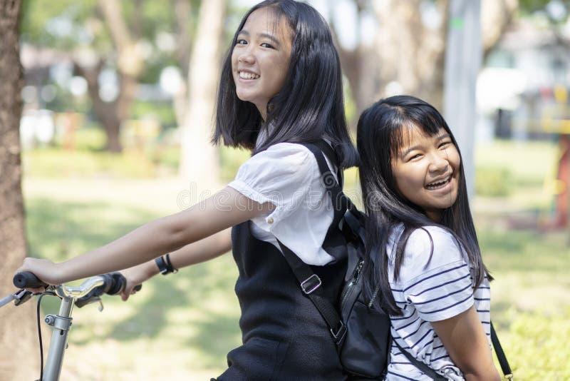 快乐的亚洲少年幸福情感骑马自行车在公园 免版税库存照片