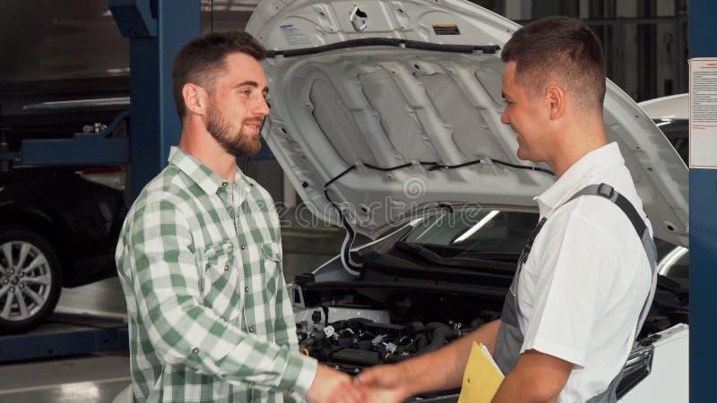 快乐的人与汽车修理师握手在服务商店 免版税库存图片