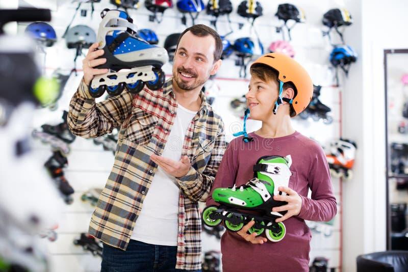 快乐的人和儿子吹嘘的路辗冰鞋 免版税库存照片