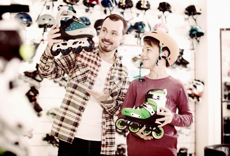 快乐的人和儿子吹嘘的路辗冰鞋 库存图片