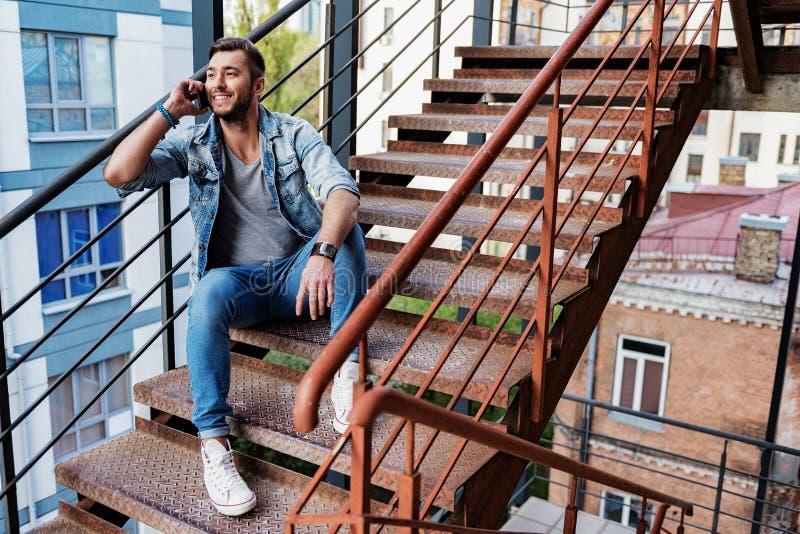 快乐的人讲话由在台阶的手机 免版税库存照片