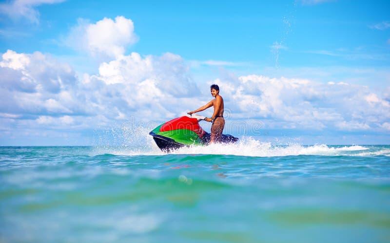 快乐的人骑马喷气机滑雪,热带海洋,活跃假期 免版税库存照片