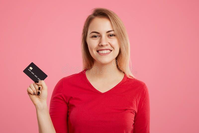 快乐的令人愉快的白肤金发的妇女拿着塑料卡片,愉快去购物和接受金钱总金额在她的帐户的,穿戴  免版税图库摄影