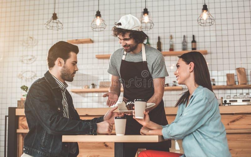 快乐的侍者服务结块和咖啡结合 免版税库存照片
