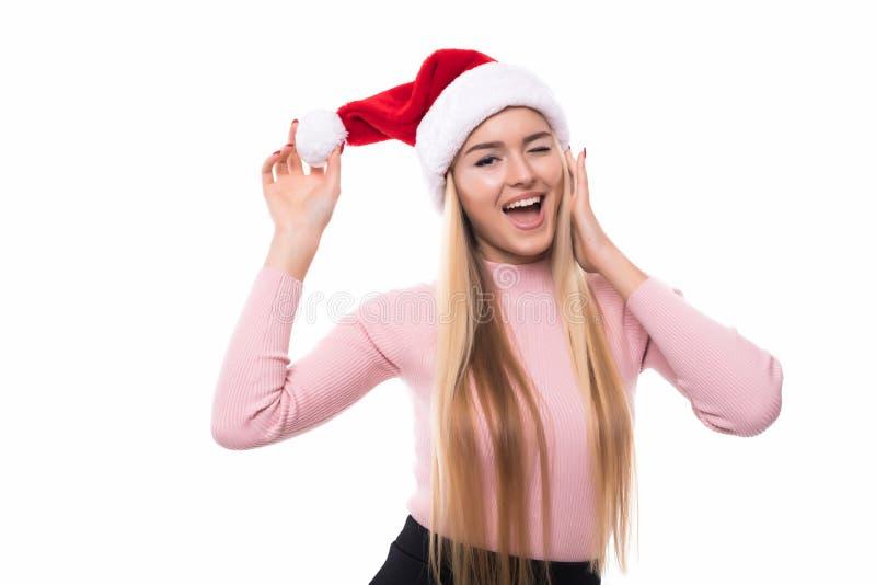 快乐的俏丽的妇女画象在白色背景隔绝的红色圣诞老人帽子的 看起来美丽的女孩愉快和兴奋 机会 库存图片