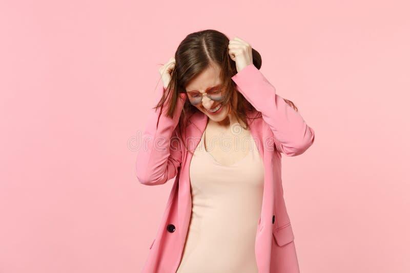 快乐的俏丽的年轻女人画象心脏玻璃的与保留在头发的被降下的头手在粉红彩笔 免版税库存照片