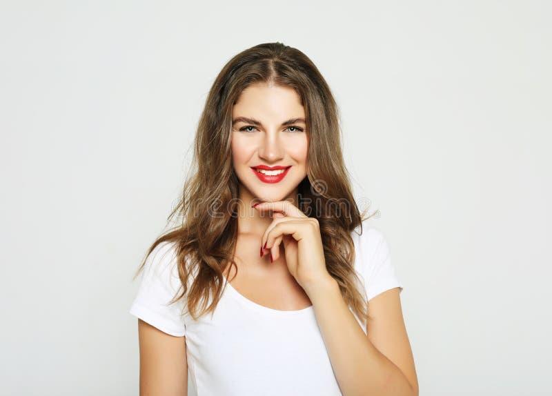 快乐的俏丽的年轻女人画象感觉快乐和笑被隔绝在白色背景 免版税库存图片