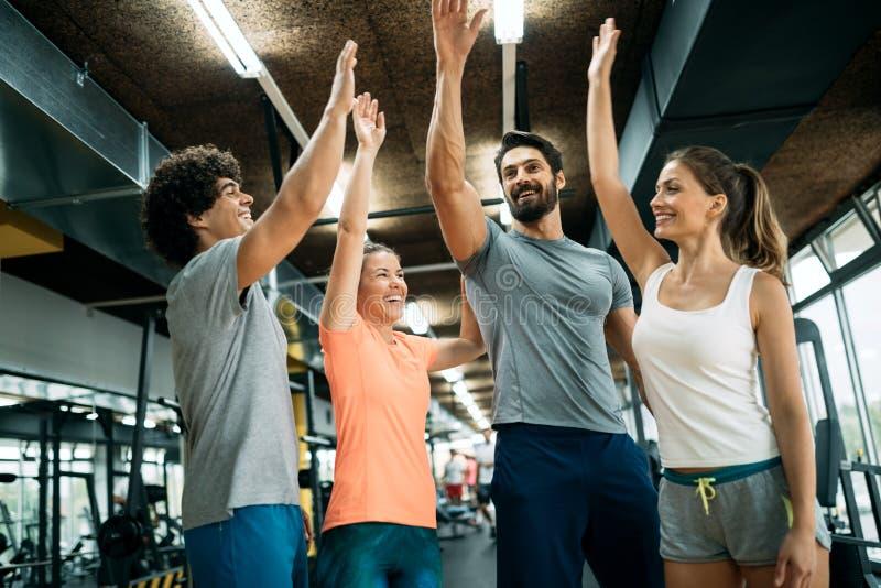 快乐的健身队的图片在健身房的 库存照片