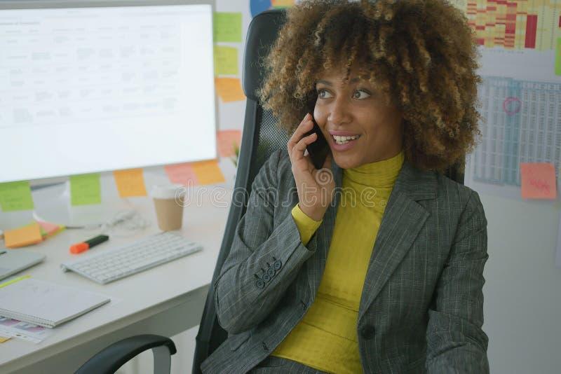 快乐的典雅的工作者谈话在电话 免版税库存图片