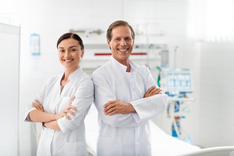 快乐的医护人员用摆在医房的横渡的手 库存图片