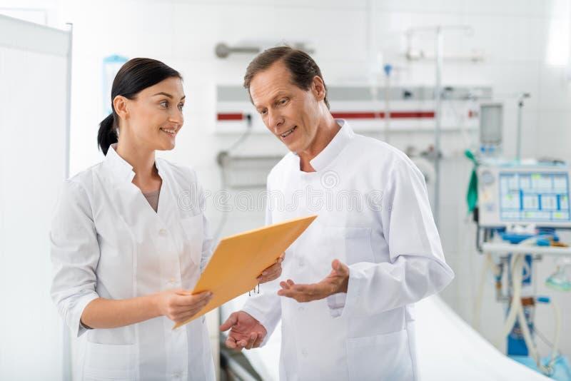 快乐的医生在护士手上的看橙色信封 库存图片