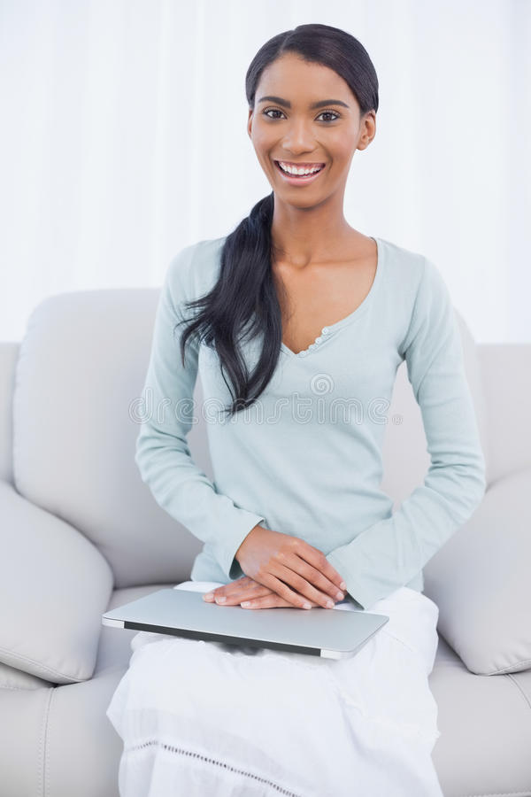 快乐的可爱的妇女坐有她的膝上型计算机的舒适沙发在她膝部 库存图片