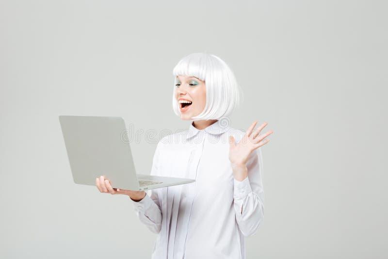 快乐的可爱的少妇身分和使用膝上型计算机 库存图片