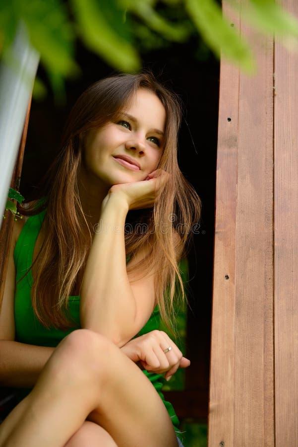 快乐的可爱的青少年的女孩室外画象庭院木头的 库存图片