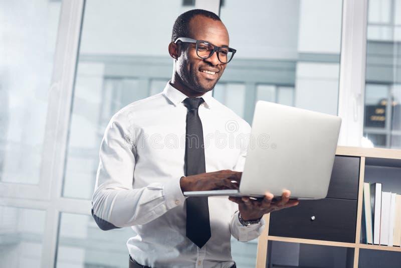快乐的合格的商人享受他的工作 免版税库存图片