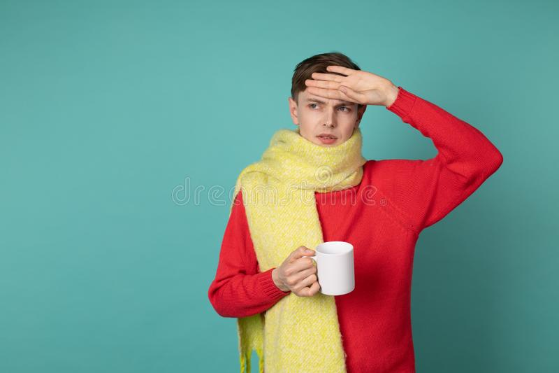 快乐的哀伤的不适的年轻人和有杯子的黄色围巾画象红色sweeater的热的茶 库存图片