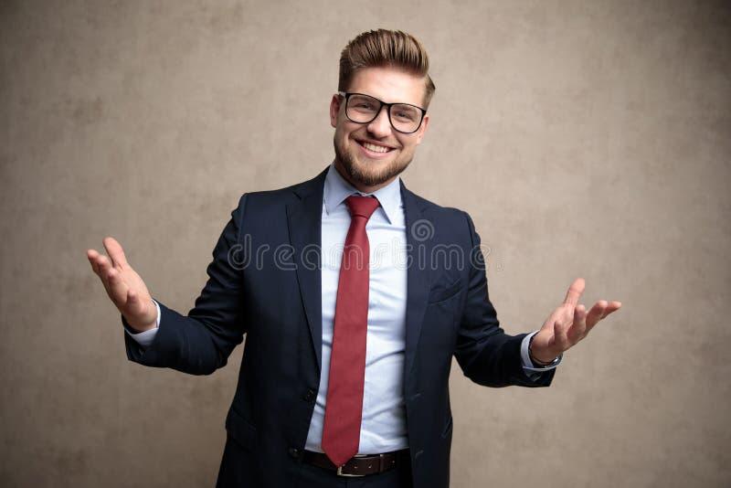 快乐的商人欢迎与大开他的胳膊 免版税图库摄影