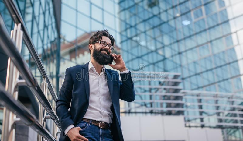 快乐的商人谈话在智能手机 库存图片