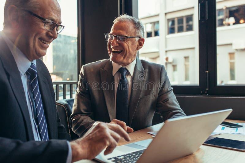 快乐的商务伙伴开会议在咖啡馆 免版税库存图片