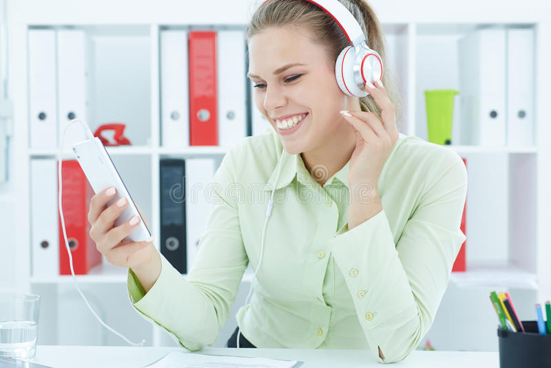年轻快乐的在耳机的秘书听的音乐在办公室 免版税图库摄影