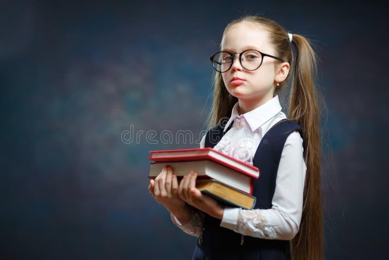 快乐的基本的女小学生举行书束 库存图片