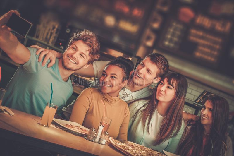 快乐的多种族朋友获得吃的乐趣在比萨店 免版税库存照片