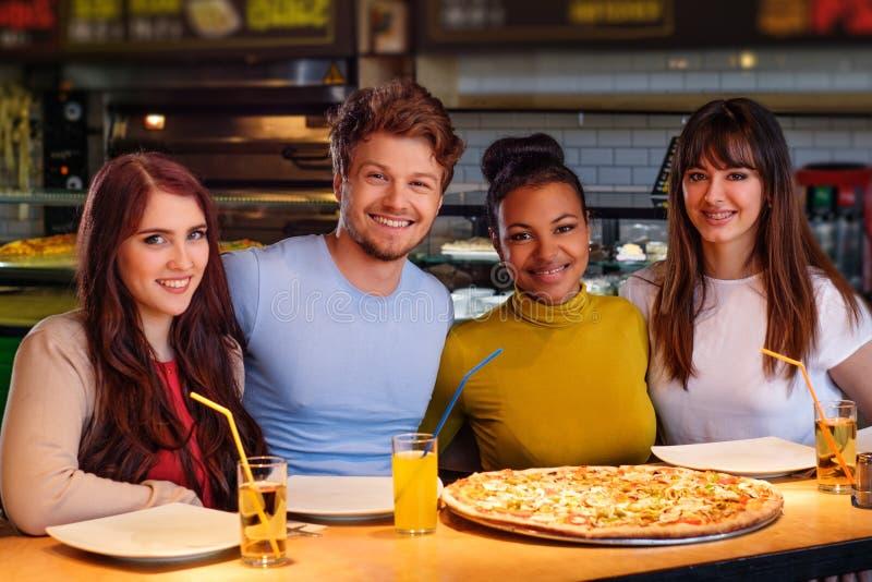 快乐的多种族朋友获得吃的乐趣在比萨店 免版税库存图片