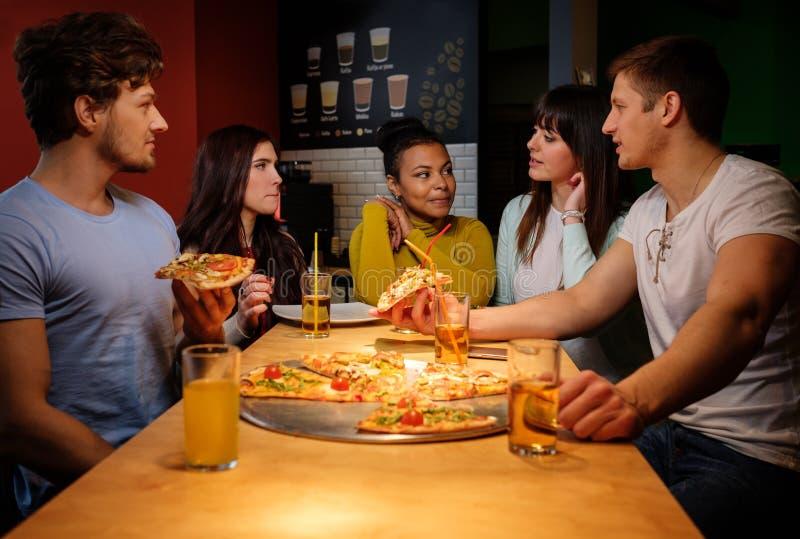 快乐的多种族朋友获得吃的乐趣在比萨店 库存照片