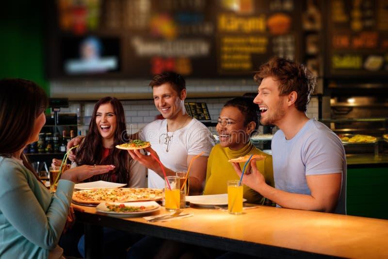 快乐的多种族朋友获得吃的乐趣在比萨店 免版税图库摄影