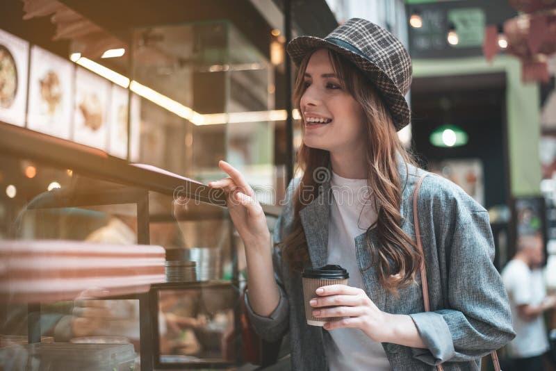 快乐的夫人用在玻璃vitrine附近的咖啡 库存图片
