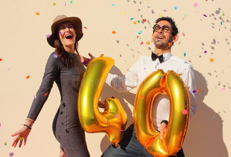 快乐的夫妇在天空中庆祝与大金黄气球和五颜六色的小的纸的一个四十年生日 图库摄影