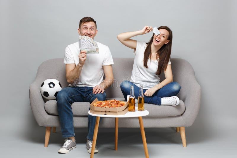 快乐的夫妇妇女人足球迷在美元钞票支持拿着信用万一银行卡,金钱爱好者的喜爱的队  免版税库存照片