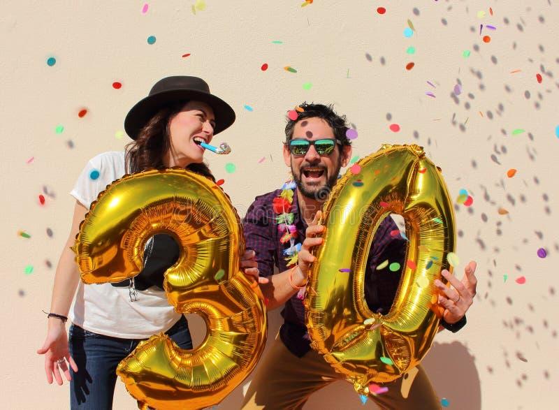 快乐的夫妇庆祝与大金黄气球的一个三十年生日 免版税库存照片