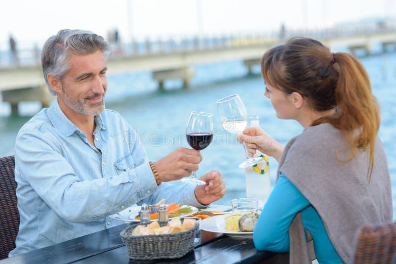 快乐的夫妇饮用的酒和享用户外 库存照片