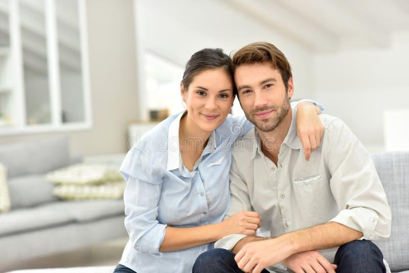 快乐的夫妇画象坐沙发 库存图片