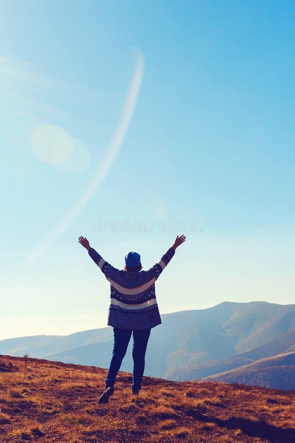 快乐的女人在自然的夕阳上 自由概念 山景美景少女 兴奋 免版税库存照片