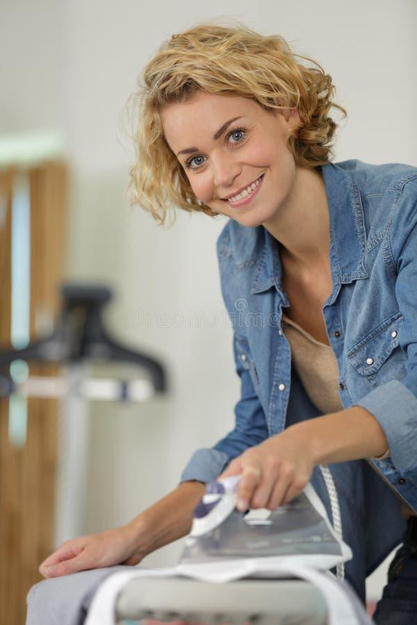 快乐的女人熨衣服 免版税库存图片